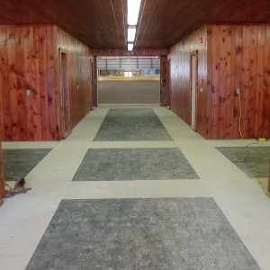 Custom Stable Interior with an Aisle with Rubber Tiles in Concrete border