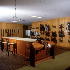 Large Tack Room inside a 48 stall barn with maple paneling and 4x8 concrete paving stones on the floor