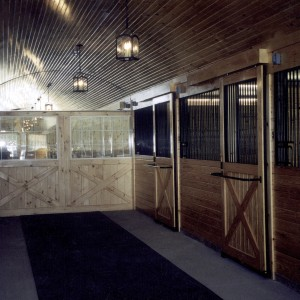 Custom Stable wood clad sliding stall doors with barrel vault ceiling and lock mats in the aisle