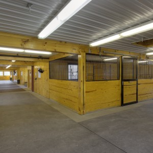 12x12 stalls with half inch thick lock mats on aisle floor - Custom Stables by Old Town Barns