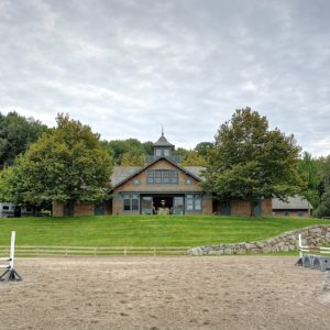 Stable Exterior with outdoor riding area in the foreground