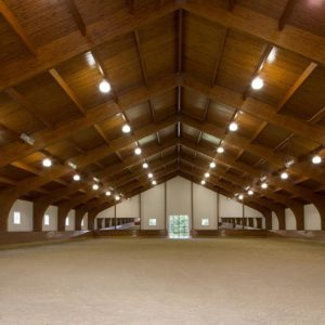 Custom Riding Arenas with Vaulted wood ceiling and white board and baton walls
