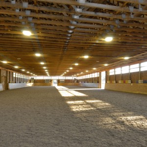 Interior of a 200x80 Indoor Riding Arena with painted steel roofing to match existing barn