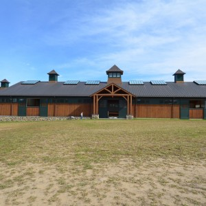 Custom Wood Clad Riding Arena with Dark Green Accents