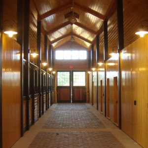 Looking down the stalls in the interior of a custom stable by Old Town Barns