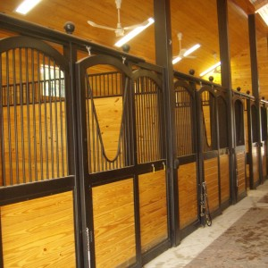 Stalls in the interior of a custom stable by Old Town Barns