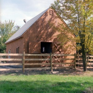 Wood Stable Exterior with a metal roof by Old Town Barns