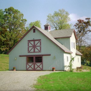 Custom Barn Design by Old Town Barns, a light green stable exterior with red trim