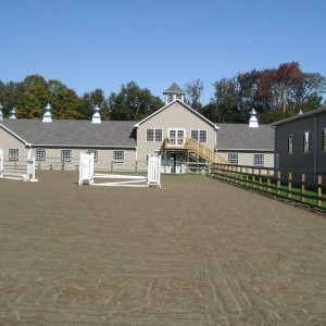 View across a riding area of a large light gray stable