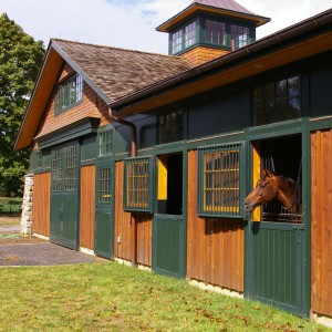 Custom Designed Stable Exterior with Cedar, Stone Accents, and Green Trim
