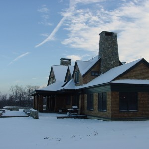 Luxury Barn Design with Cedar Shingles and Green Trim in the Snow