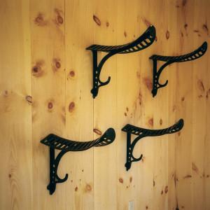 Beautiful antique style aluminum powder coated saddle racks hanging in custom stable