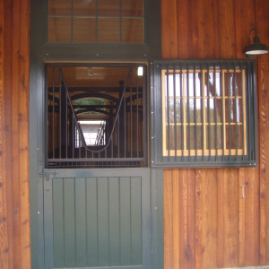 Wood barn with green accents showing a horse stall window open looking through to the other side